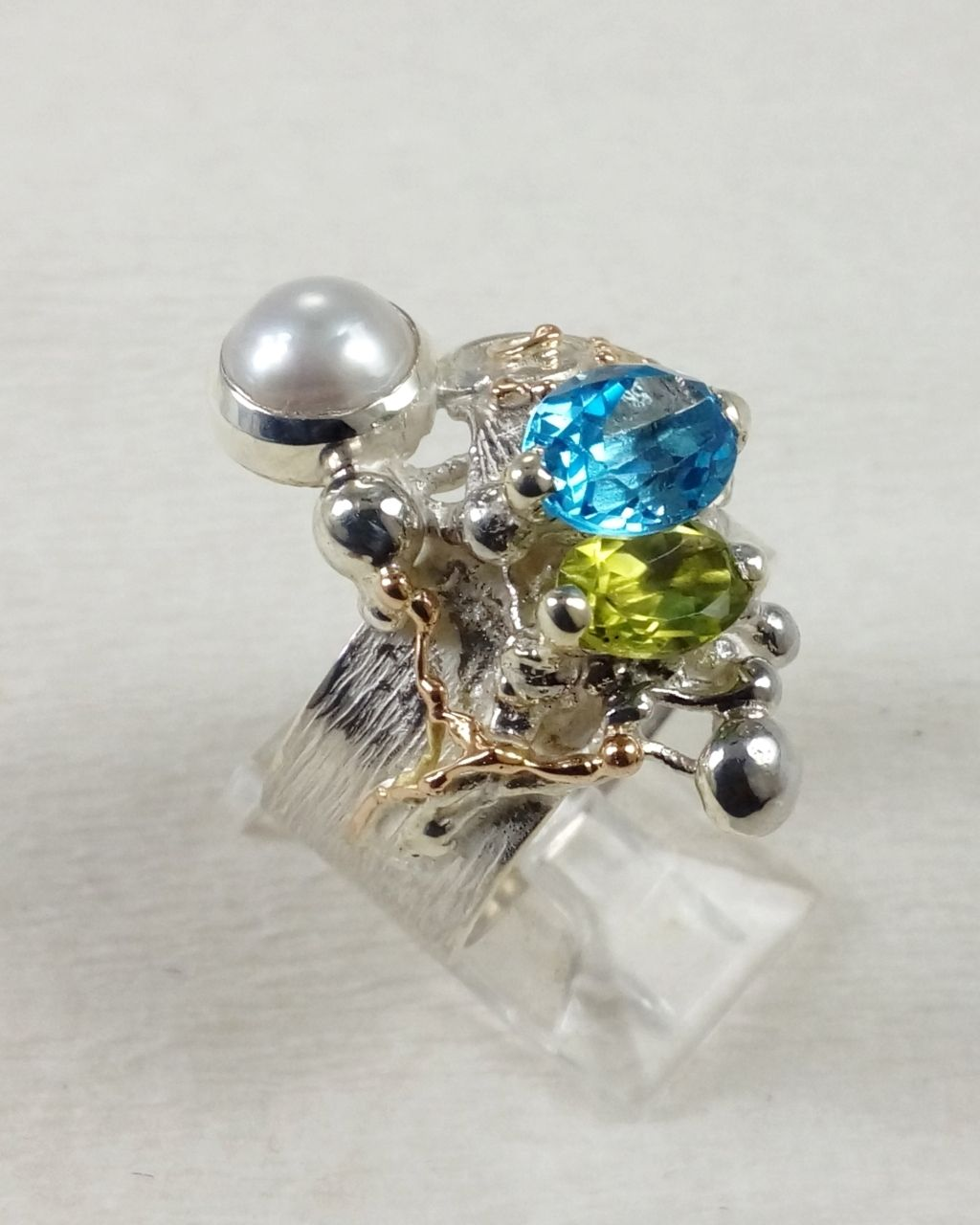 Gregory Pyra Piro ring 3025, jewellery artist in Europe, jewellery maker in Europe, original handcrafted jewellery in Europe, ring with blue topaz and peridot, ring with gemstones and pearl, rings sold in art and craft galleries, handcrafted jewellery made during lockdown